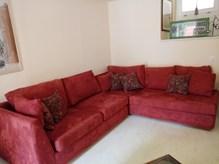 Πωλείται γωνιακός καναπές χρώματος μπορντώ, με ύφασμα σουέτ, με πέντε μαξιλάρια